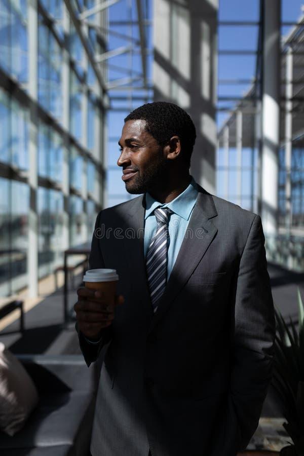 Homem de negócios afro-americano com o copo de café que olha afastado no escritório fotografia de stock royalty free