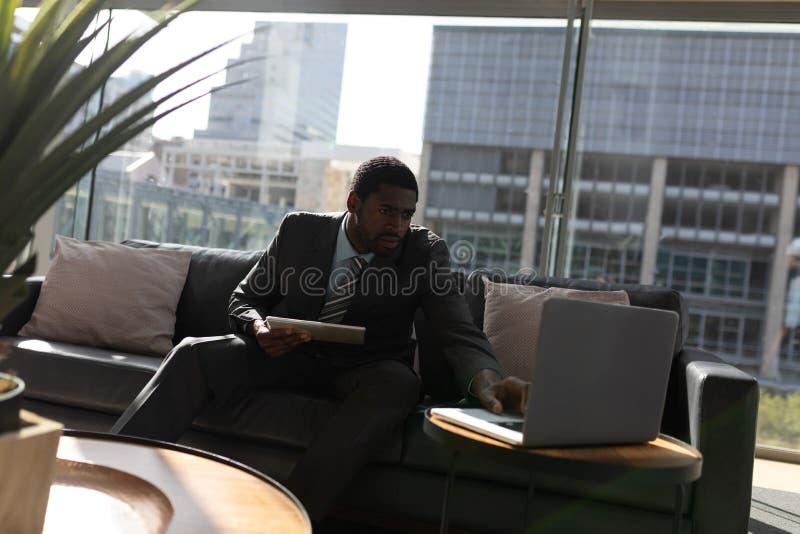 Homem de negócios afro-americano com a tabuleta digital que trabalha no portátil no sofá no escritório fotografia de stock