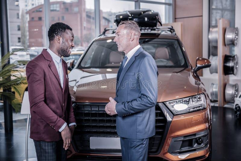 Homem de negócios afro-americano considerável que compra o carro novo grande fotos de stock royalty free