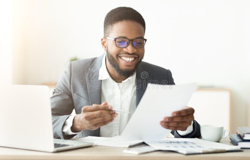 Homem de negócios afro-americano considerável que trabalha em documentos da leitura do escritório imagem de stock royalty free
