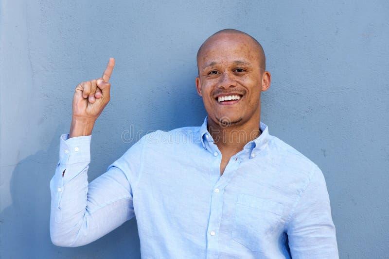 Homem de negócios afro-americano de sorriso que aponta o dedo acima imagem de stock
