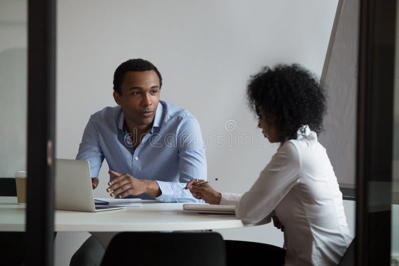 Homem de negócios afro-americano e mulher de negócios que discutem o projeto, planeamento imagens de stock royalty free