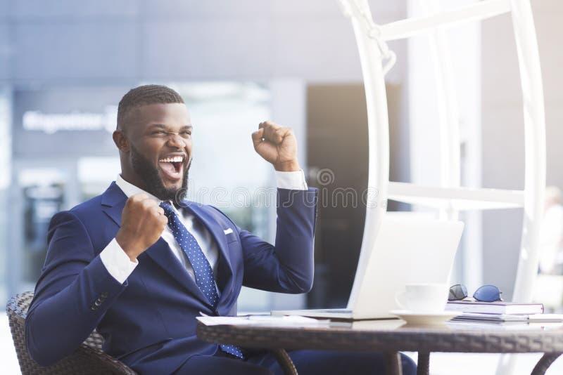 Homem de negócios afro-americano feliz Shaking Clenched Fists no café exterior imagens de stock