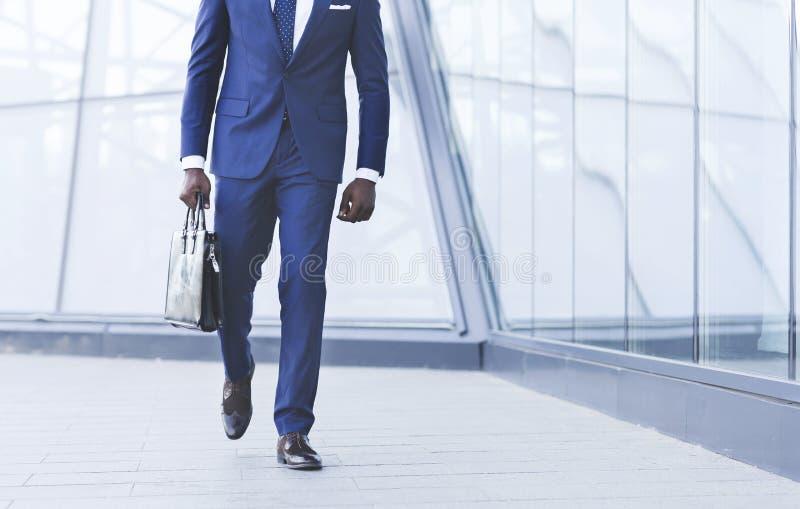 Homem de negócios afro-americano irreconhecível Walking With Briefcase na cidade imagens de stock royalty free