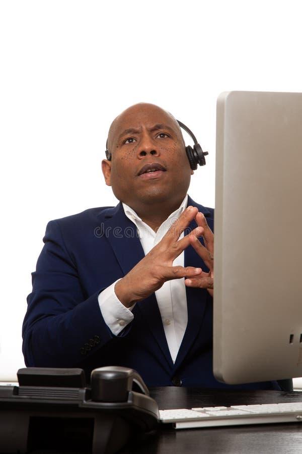 Homem de negócios afro-americano Listening Through Headset fotos de stock royalty free