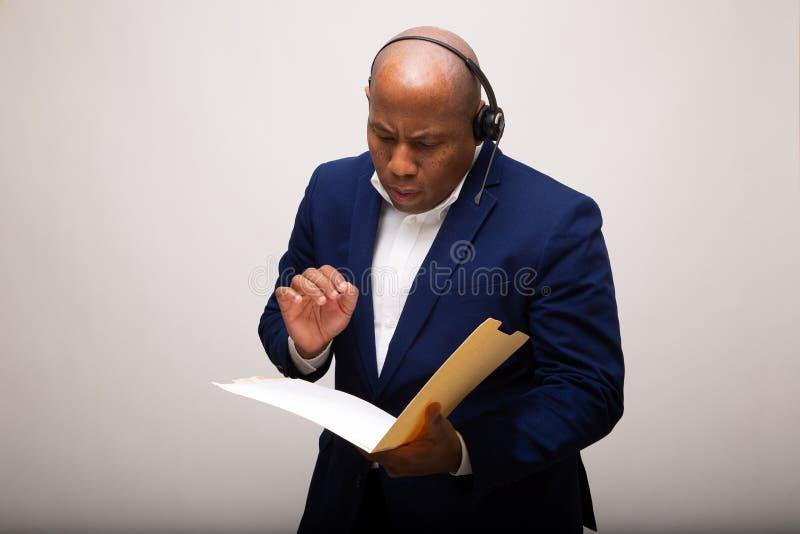 Homem de negócios afro-americano Looks Through File foto de stock royalty free