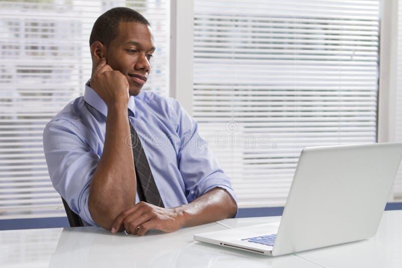 Homem de negócios afro-americano na mesa com o computador, horizontal foto de stock royalty free