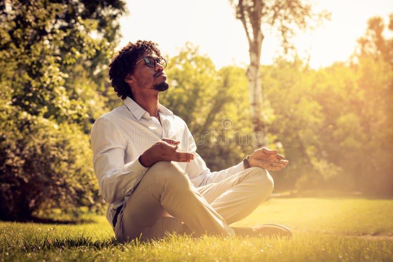 Homem de negócios afro-americano na posição de Lotus no por do sol fotos de stock royalty free