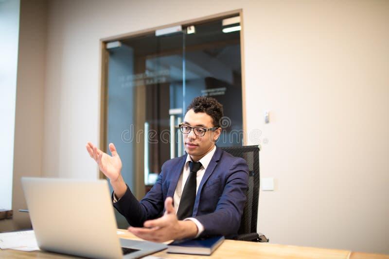 Homem de negócios afro-americano no terno oficial luxuoso que acumula a conversação video em linha no laptop com sócio internacio imagens de stock royalty free
