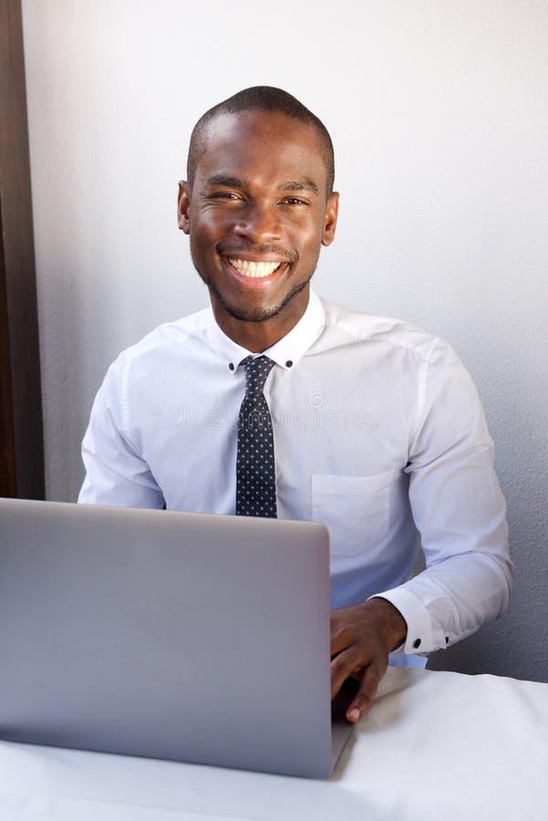 Homem de negócios afro-americano novo considerável que trabalha com portátil imagens de stock royalty free