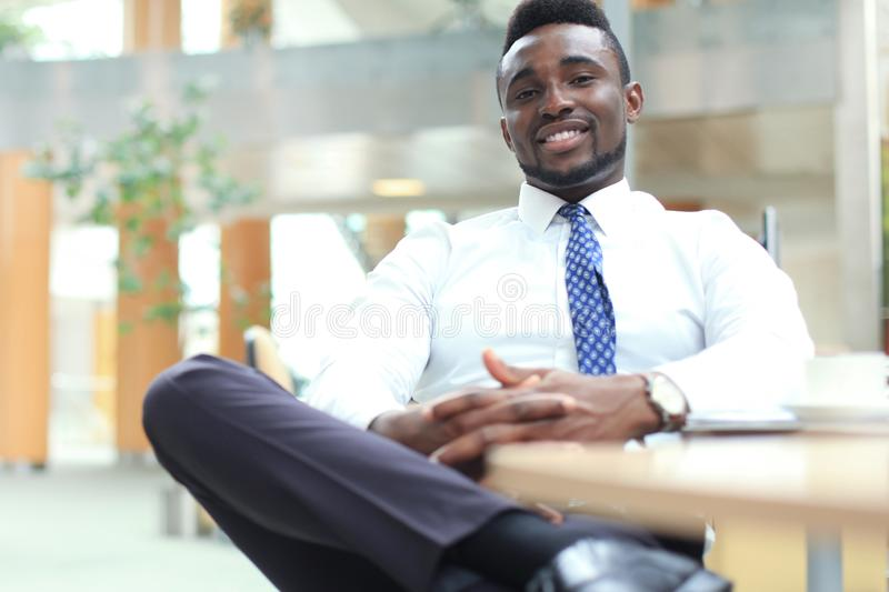 Homem de negócios afro-americano novo feliz que olha a câmera no local de trabalho no escritório fotos de stock