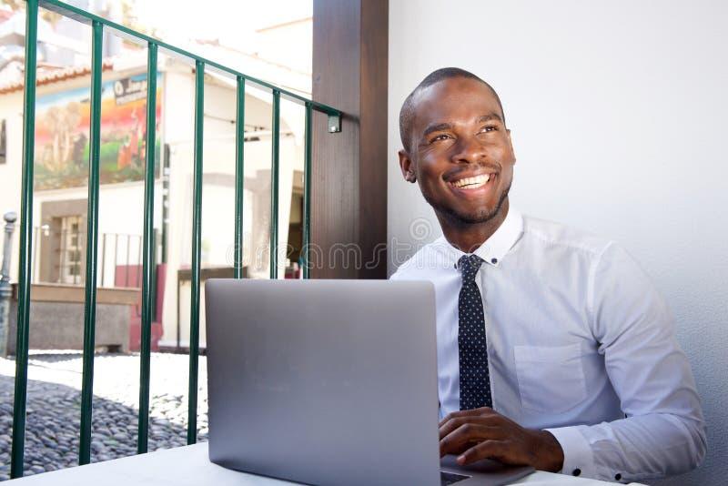 Homem de negócios afro-americano novo feliz que trabalha durante a pausa para o almoço no restaurante fotografia de stock