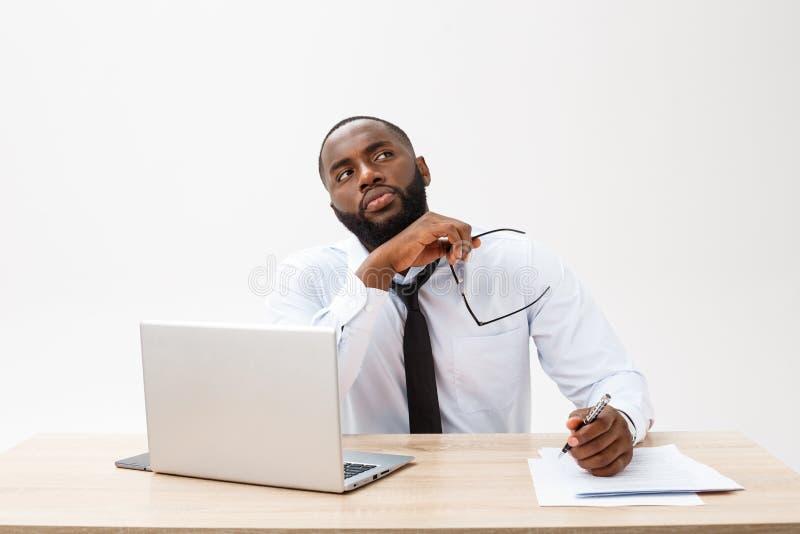 Homem de negócios afro-americano novo pensativo que trabalha no laptop fotografia de stock royalty free