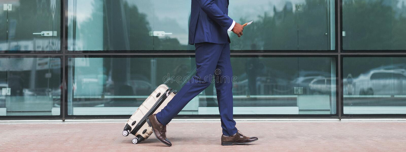 Homem de negócios afro-americano que anda com a bagagem, chegando no aeroporto foto de stock royalty free