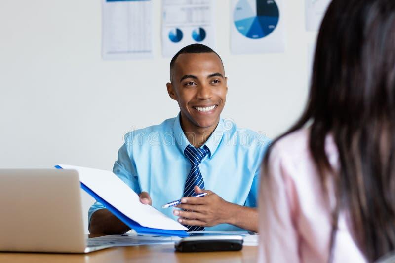 Homem de negócios afro-americano que apresenta o contato para o trabalho novo fotos de stock royalty free