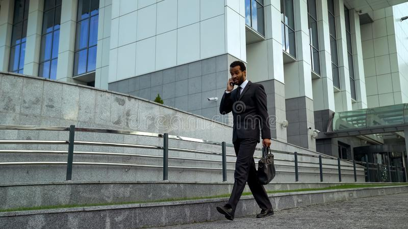Homem de negócios afro-americano que fala no telefone, forçado e sobrecarregado, fim do prazo fotos de stock