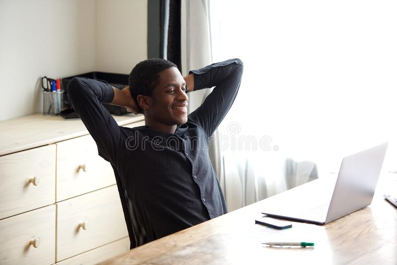 Homem de negócios afro-americano que relaxa com mãos atrás da cabeça no escritório fotos de stock royalty free