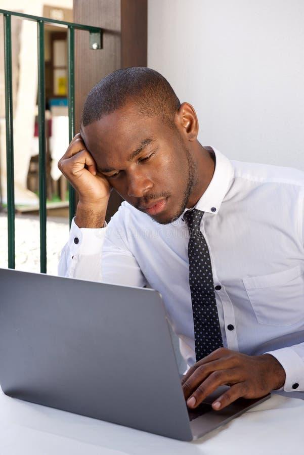 Homem de negócios afro-americano que senta-se na tabela e que olha o portátil foto de stock