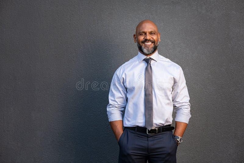 Homem de negócios afro-americano que sorri em cinzento foto de stock royalty free