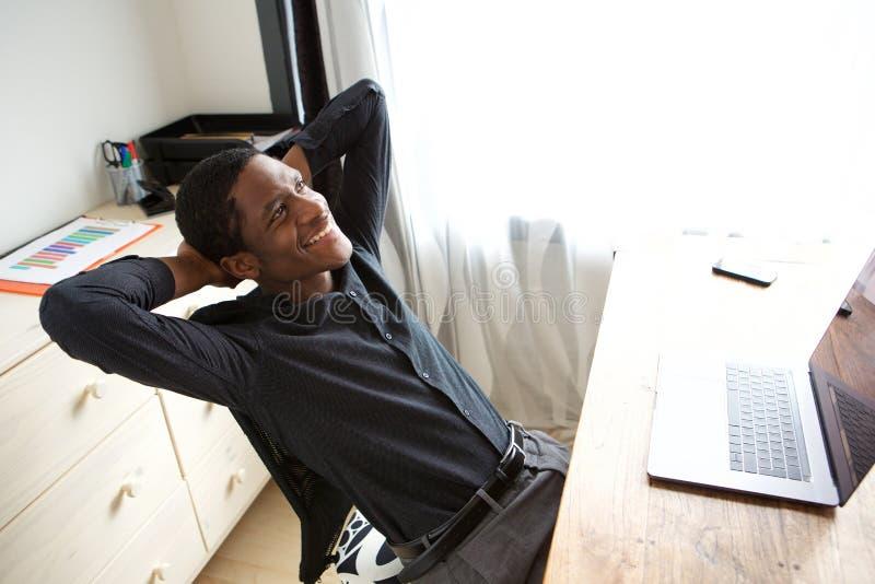 Homem de negócios afro-americano relaxado que senta-se na mesa com mãos atrás da cabeça fotos de stock royalty free
