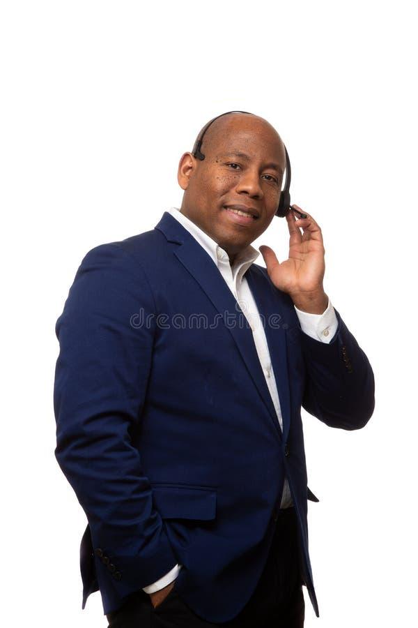 Homem de negócios afro-americano de sorriso Listens Through Headset foto de stock royalty free