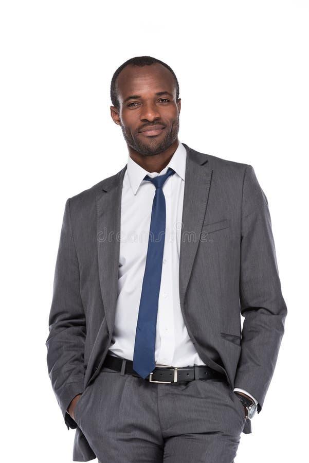 homem de negócios afro-americano de sorriso no terno com mãos em uns bolsos fotos de stock royalty free
