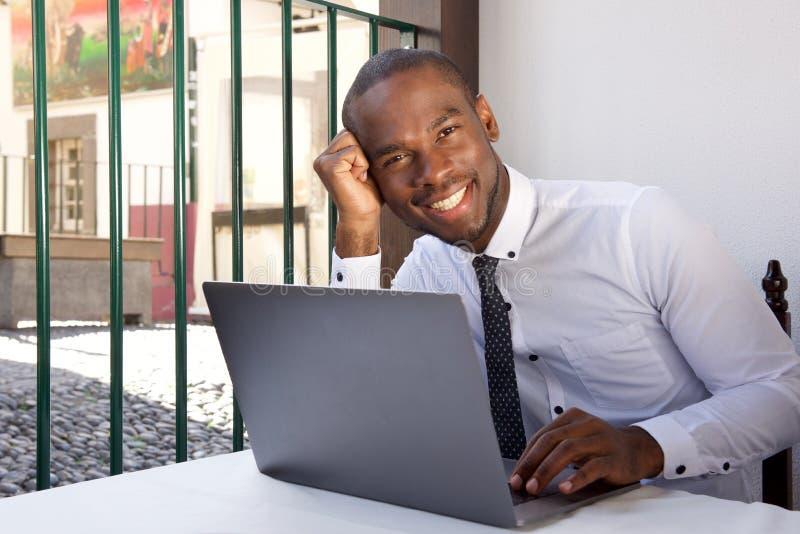 Homem de negócios afro-americano de sorriso que senta-se na tabela com laptop imagem de stock royalty free