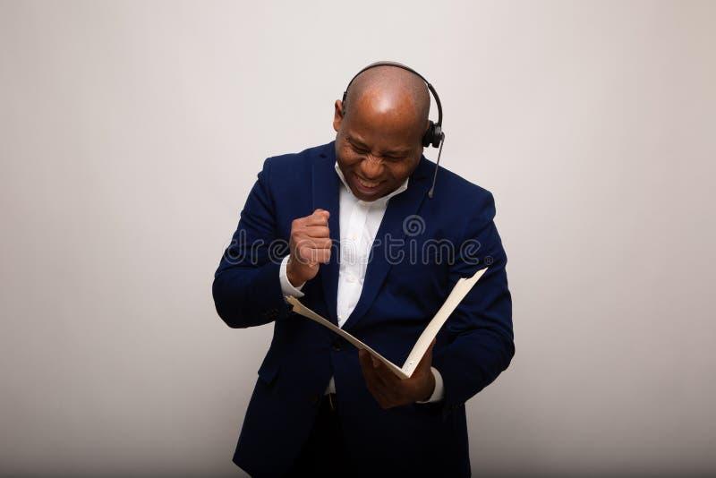 Homem de negócios afro-americano triunfante Looks Through File fotografia de stock