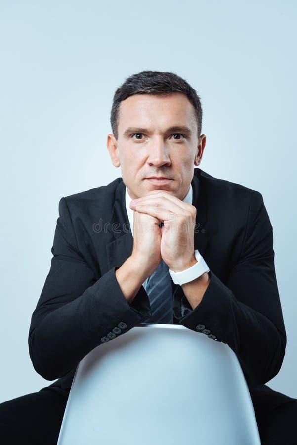 Homem de negócios agradável sério que inclina-se na cadeira foto de stock royalty free