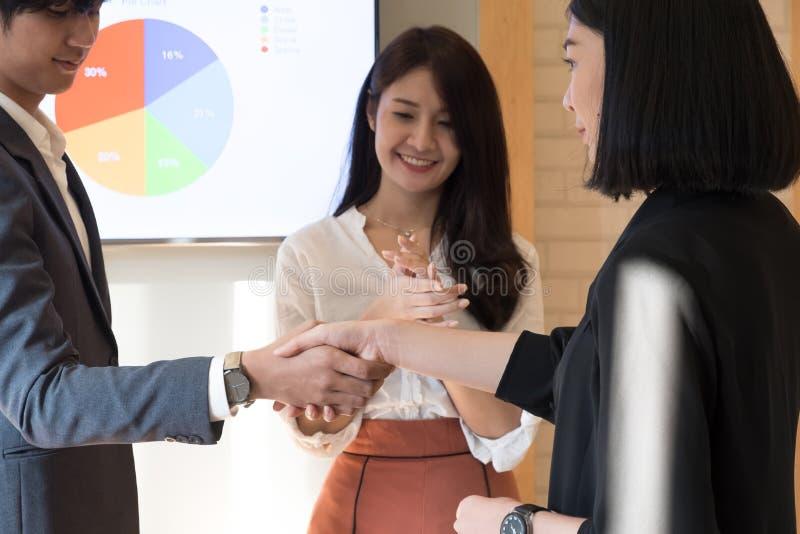 Homem de negócios alegre que agita as mãos com mulher de negócios quando busi imagens de stock royalty free