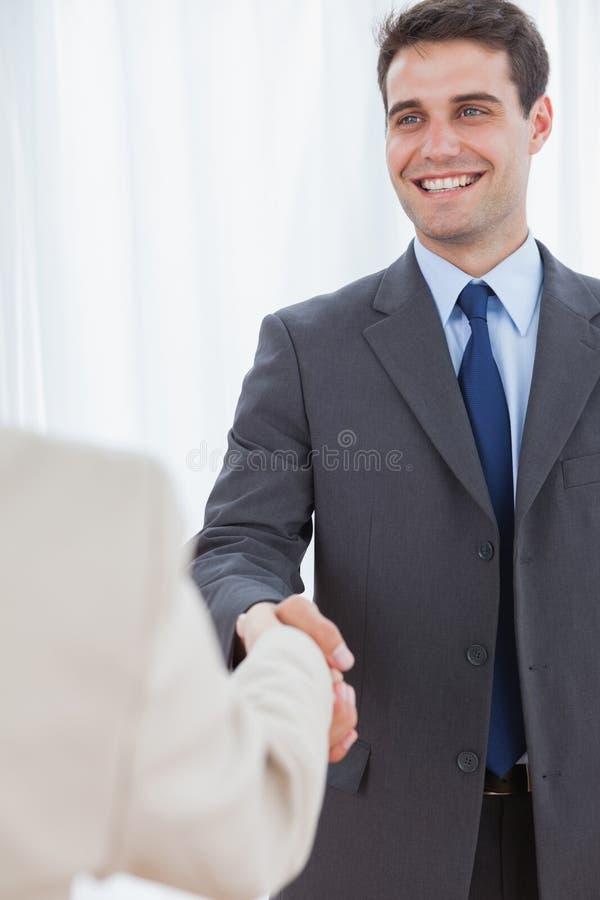 Homem de negócios alegre que agita as mãos com seu workmate novo fotos de stock