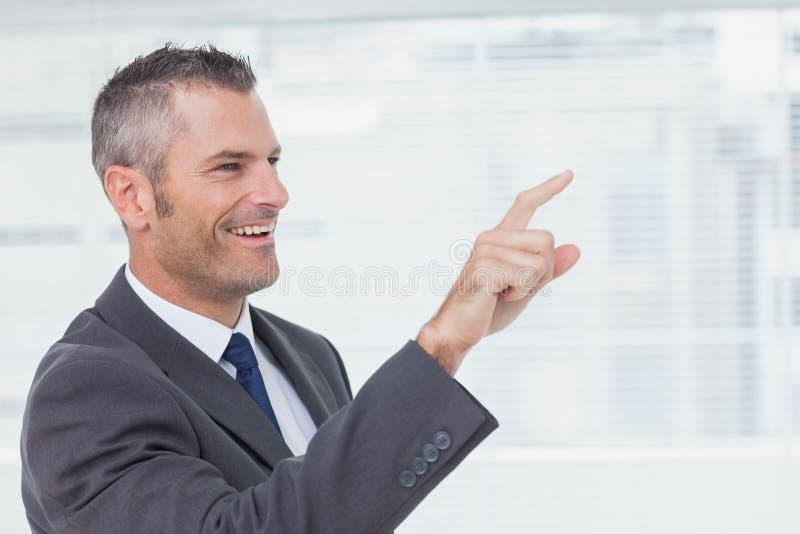 Homem de negócios alegre que aponta ao olhar afastado foto de stock