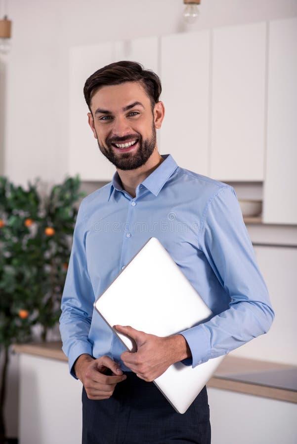 Homem de negócios alegre que guarda seu portátil fotografia de stock royalty free