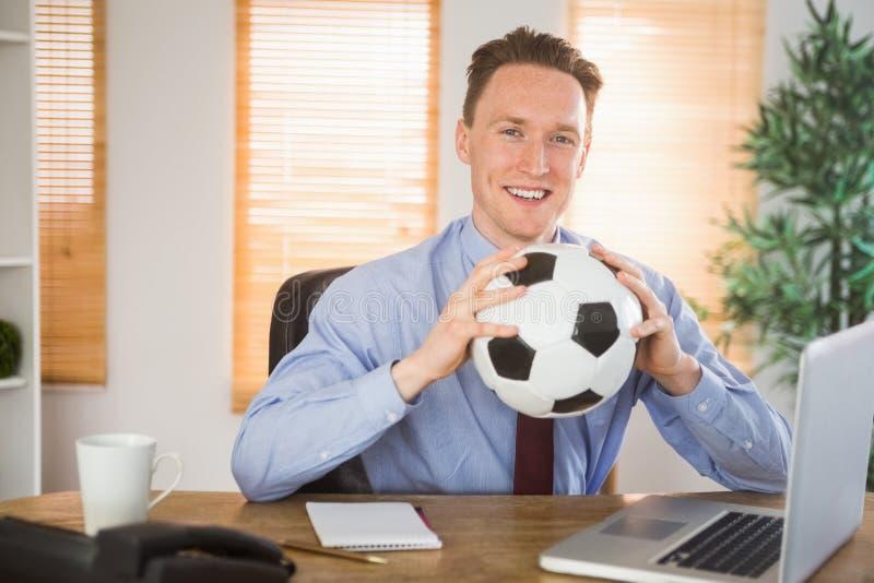 Homem de negócios alegre que guarda uma bola de futebol imagens de stock royalty free
