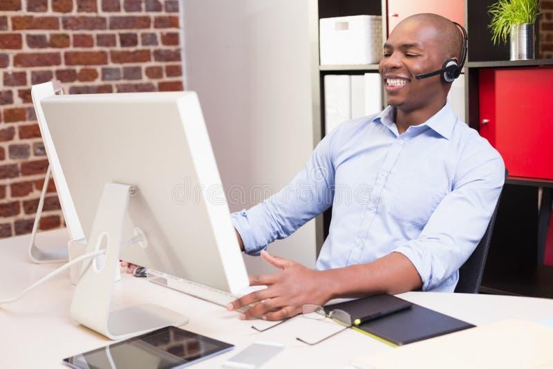 Homem de negócios alegre que usa o computador no escritório fotografia de stock royalty free