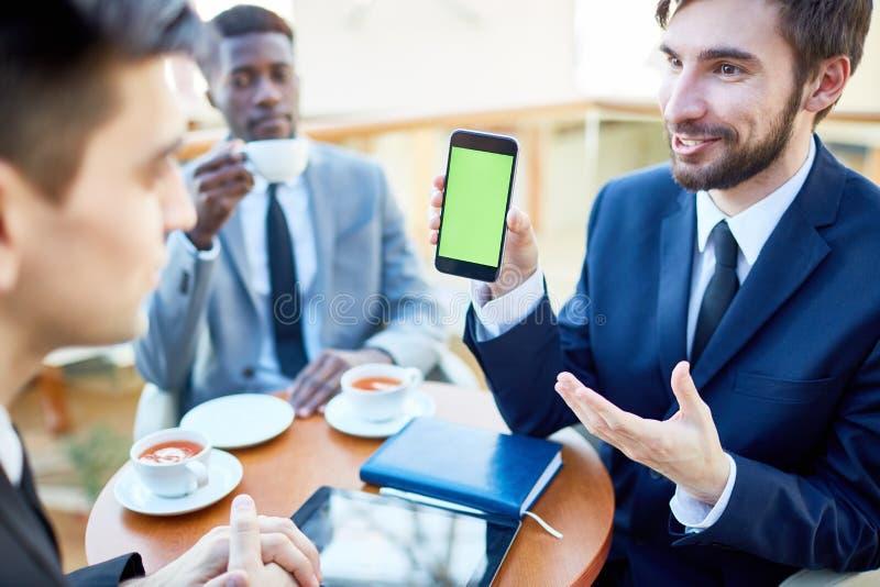 Homem de negócios alegre Showing Mobile App aos colegas fotos de stock