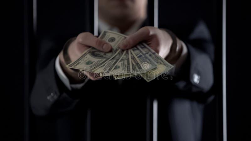 Homem de negócios algemado que guarda cédulas do dólar, fraude, lavagem de dinheiro fotografia de stock