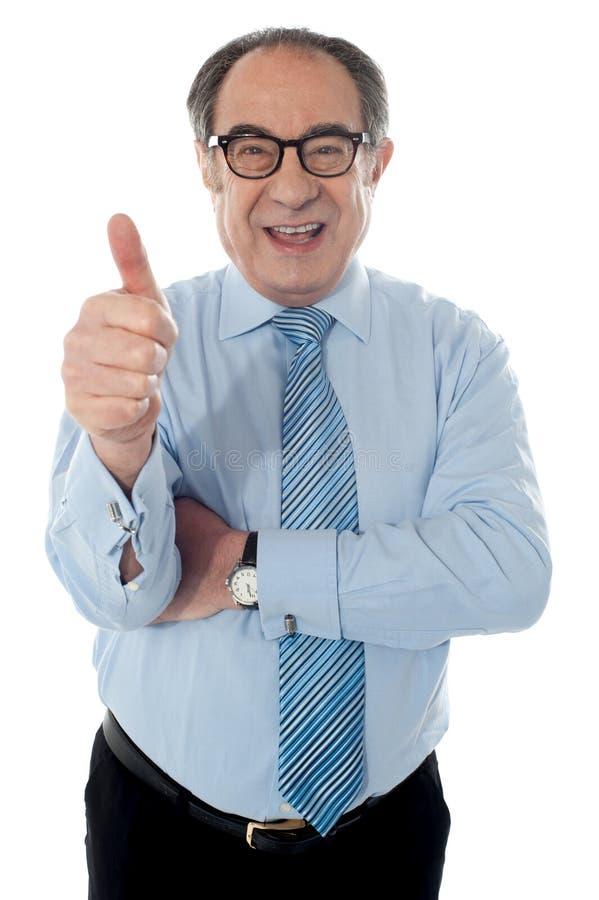 Homem de negócios amadurecido que gesticula o thumbs-up imagens de stock royalty free
