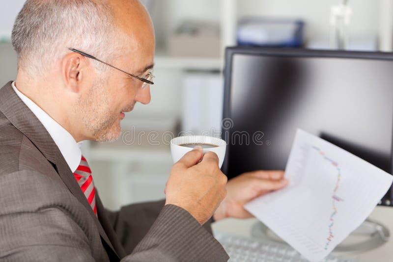 Homem de negócios Analyzing Line Graph ao guardarar o copo de café fotografia de stock royalty free