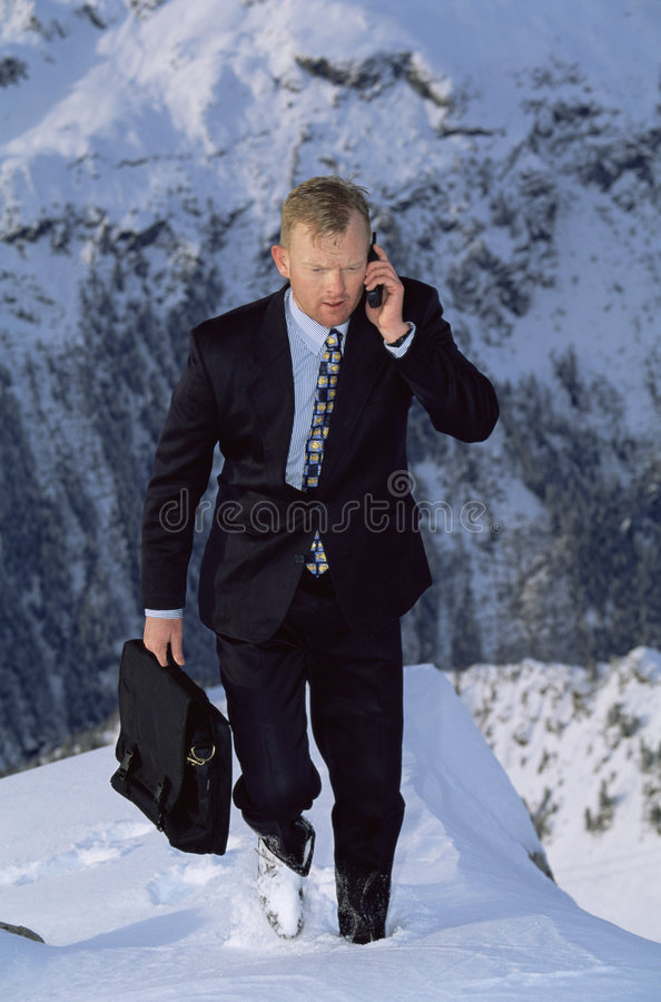 Homem de negócios ao ar livre na montanha nevado usando o telefone foto de stock