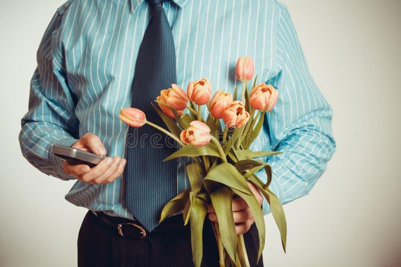 Homem de negócios ao telefonar e ao guardar a tulipas foto de stock royalty free
