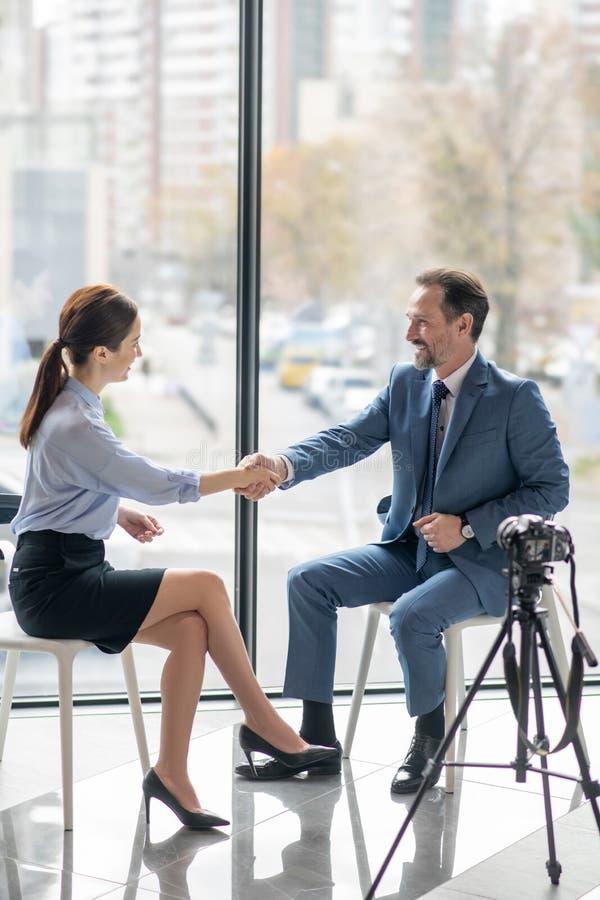 Homem de negócios a apertar a mão do seu jornalista e a sorrir depois de uma boa conversa imagens de stock
