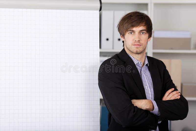 Homem de negócios With Arms Crossed em Front Of Flip Chart imagens de stock