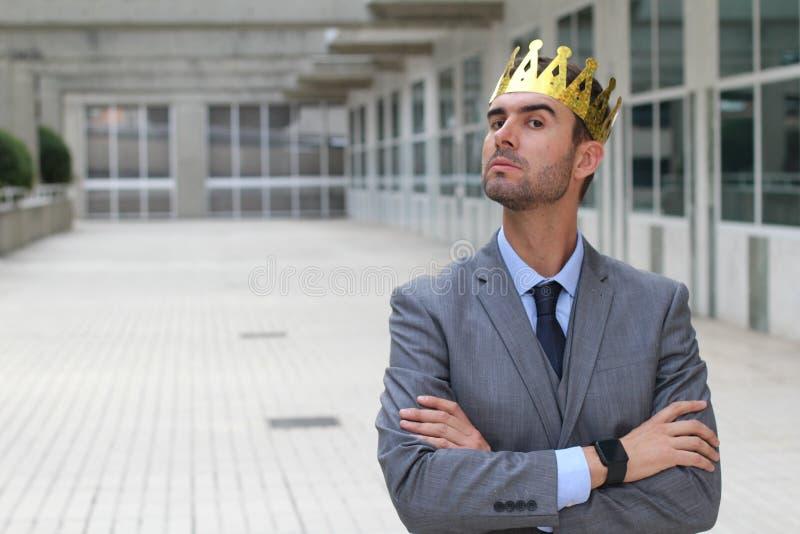 Homem de negócios arrogante com uma coroa no espaço de escritórios imagens de stock royalty free