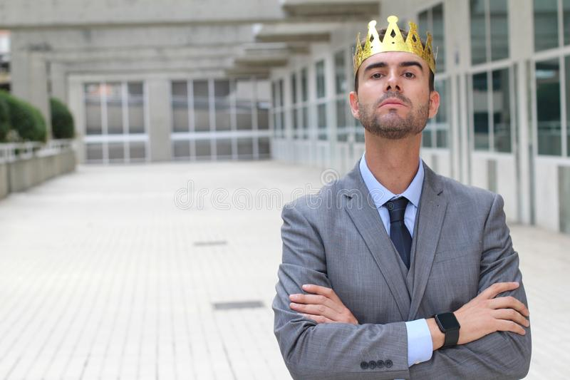 Homem de negócios arrogante com uma coroa no espaço de escritórios fotografia de stock