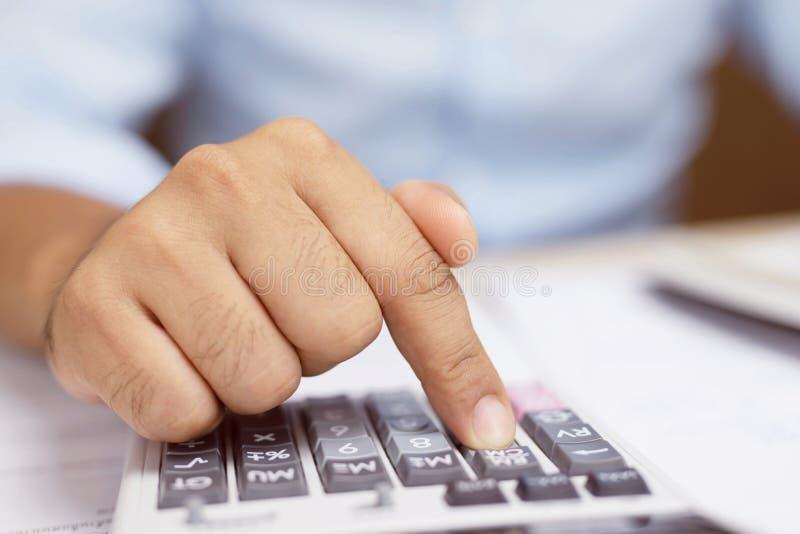 Homem de negócios ascendente próximo da mão que usa a calculadora eletrônica que calcula o número dos dados na mesa de escritório fotos de stock royalty free