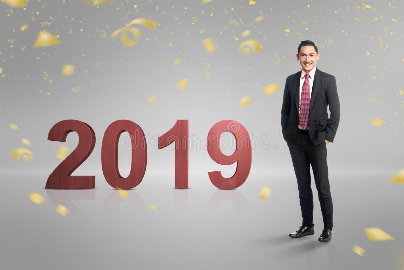 Homem de negócios asiático considerável que está ao lado do número 2019 imagens de stock royalty free