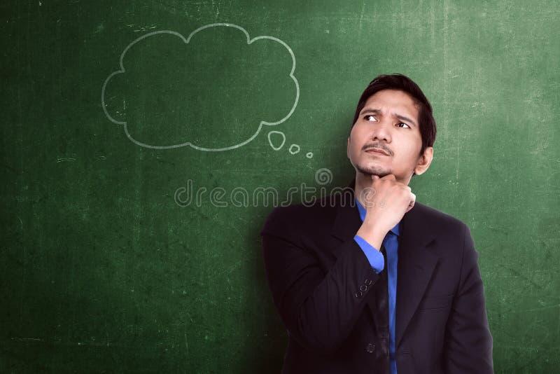 Homem de negócios asiático considerável que pensa com bolha do pensamento fotografia de stock royalty free