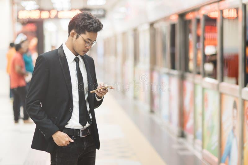 Homem de negócios asiático do moderno novo que usa o smartphone ao esperar um trem no metro Conceito da tecnologia sem fios, móve foto de stock