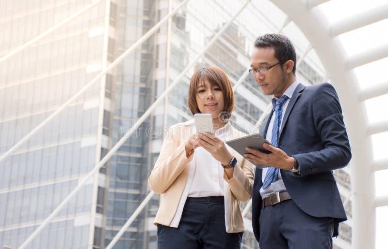 Homem de negócios asiático e mulher de negócios que discutem ideias com a utilização da tabuleta e do telefone celular digitais fotos de stock royalty free